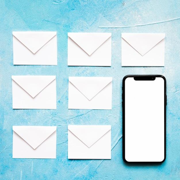 Значки сообщений белый конверт бумаги с мобильного телефона на синем фоне Бесплатные Фотографии