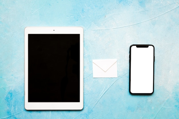 Message icons white paper envelope with digital tablet and cellphone on painted blue backdrop Free Photo