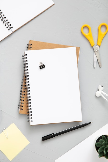 Messy arrangement of desk elements with empty notebook Free Photo