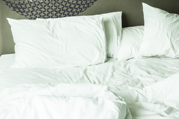Messy bed with white sheets Free Photo