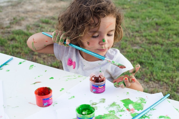 Messy girl painting on canvas in park Free Photo