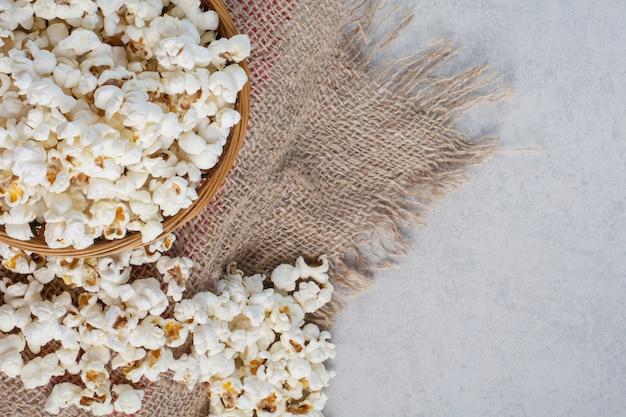 Mucchio disordinato di popcorn accanto a una ciotola piena su un pezzo di stoffa su marmo. Foto Gratuite