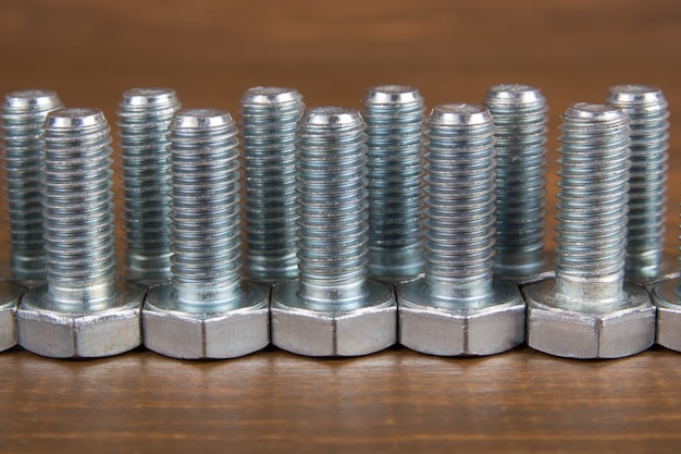 Metal bolts on a wooden Premium Photo