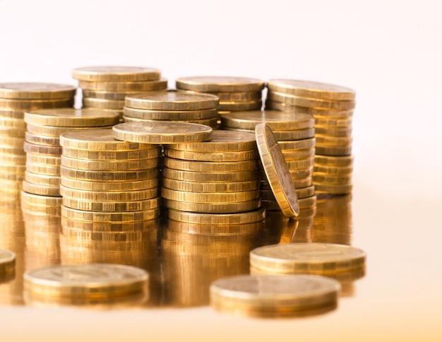 Металлические монеты сложены на золотом столе. Premium Фотографии