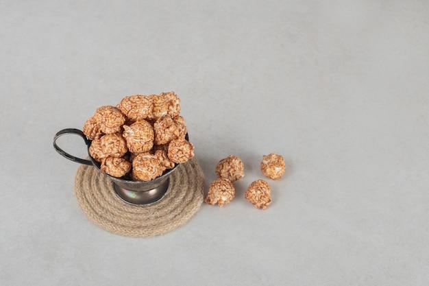 Tazza di metallo traboccante di popcorn canditi marroni su marmo. Foto Gratuite