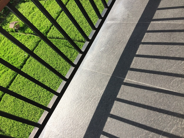 Metal fence shadow on the balcony with a view of a grassy field on a sunny day Free Photo