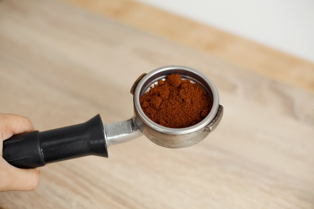 Metal holder for the coffee machine with ground coffee inside lies on a wooden table Premium Photo