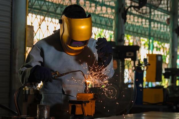 Metal industry welders in industrial plants standard protective equipment, gloves and masks. Premium Photo