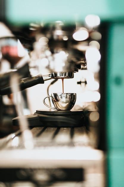 Macchina per caffè in metallo di grandi dimensioni che versa il caffè in una tazza di metallo Foto Gratuite