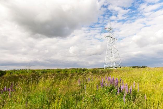 현장의 전선 용 금속 기둥. 여름에 클로즈업. 기둥에 초점을 맞 춥니 다. 백그라운드에서 구름과 하늘 프리미엄 사진
