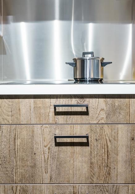 Metal pot on induction hob in modern kitchen. Premium Photo