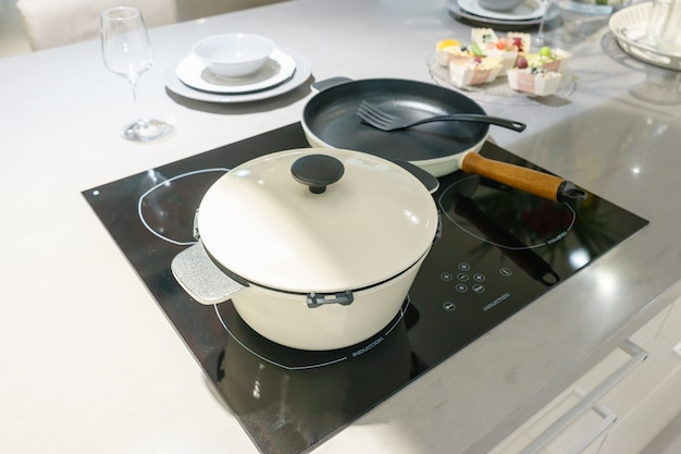 Metal pot on induction hob in modern kitchen. Premium Photo