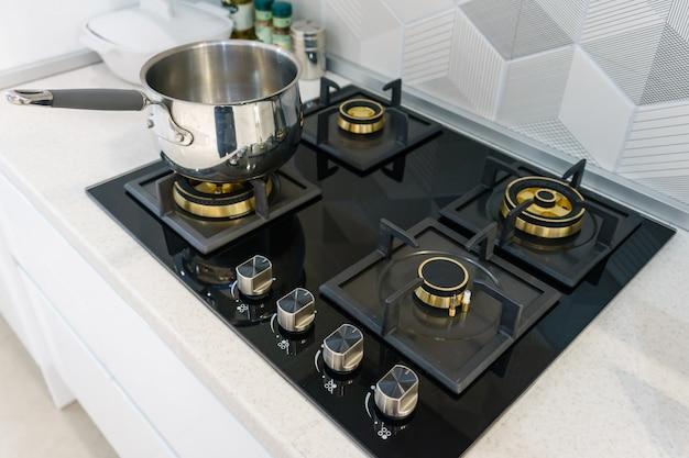 Metal pot on induction hob in modern kitchen Premium Photo