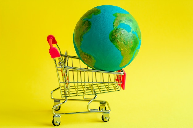 Metal shopping cart with a model of the planet earth Premium Photo