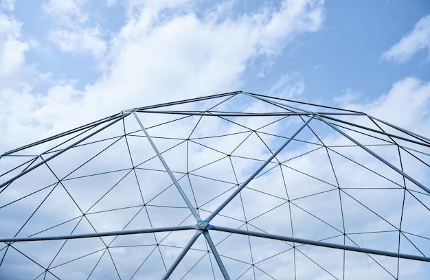 白い雲と青い空を背景の金属構造。 無料写真