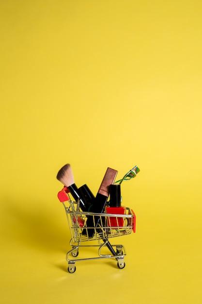 Metal вагонетка с косметиками на желтом цвете изолировала предпосылку с космосом для текста. вертикальная ориентация Premium Фотографии