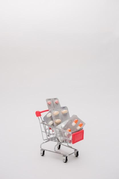 Metal вагонетка с таблетками на предпосылке изолированной белизной. Premium Фотографии