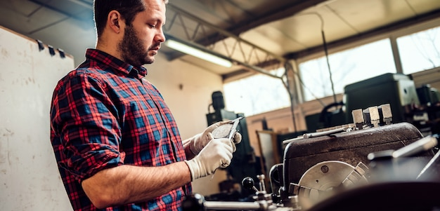 Metal worker turner using caliper by the lathe machine Premium Photo