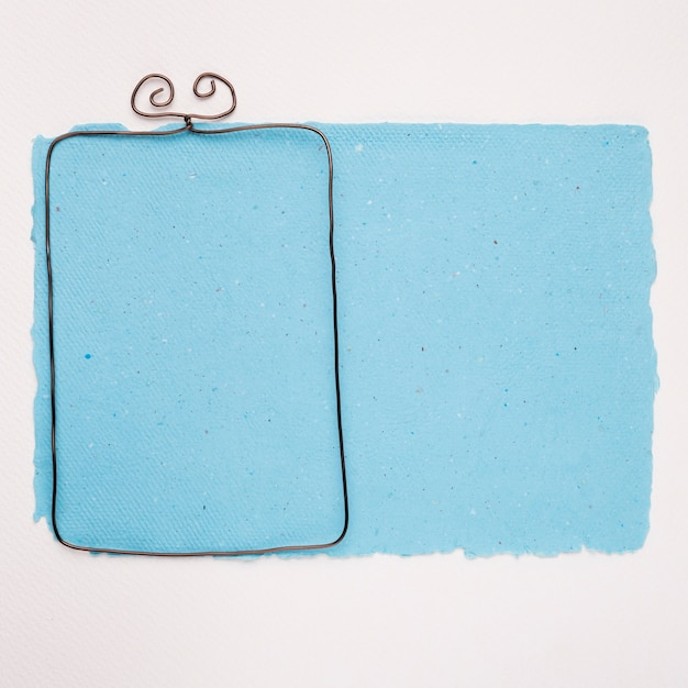 Metallic empty frame on blue paper over white background Free Photo