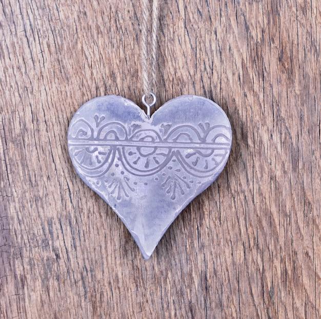 Metallic heart shaped on a plank Premium Photo