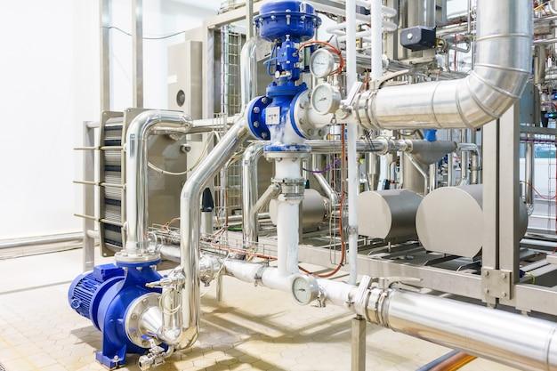 Metallic plate in heat exchange machine and pump in the food industrial plant Premium Photo