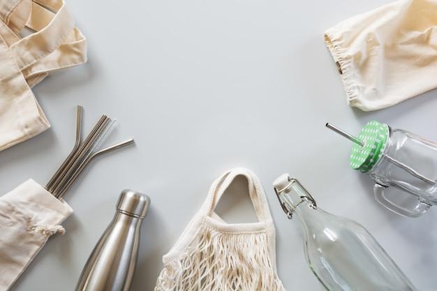 Metallic straws, cotton bag, glass and metal bottle on grey. Premium Photo