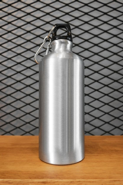 Metallic water bottle and carabiner on wood shelf background. Premium Photo