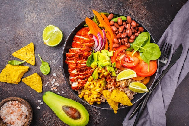 Mexican chicken burrito bowl with rice, beans, tomato, avocado,corn and spinach. mexican cuisine food concept. Premium Photo