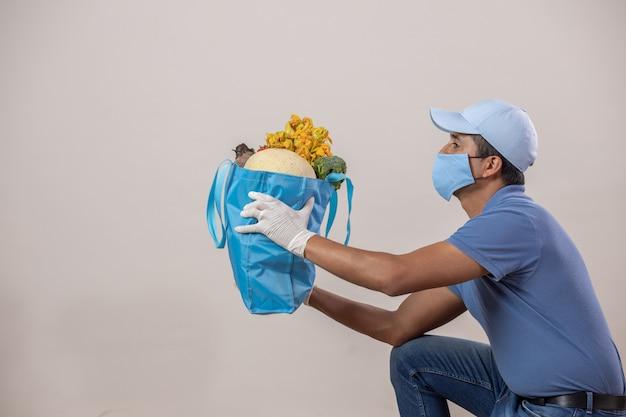メキシコは果物と野菜を配達し、口カバーと手袋と膝にキャップを付けます Premium写真