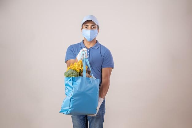 メキシコの配達人は、フェイスマスクと手袋を身に着けている果物と野菜で生態学的なバッグをロード Premium写真