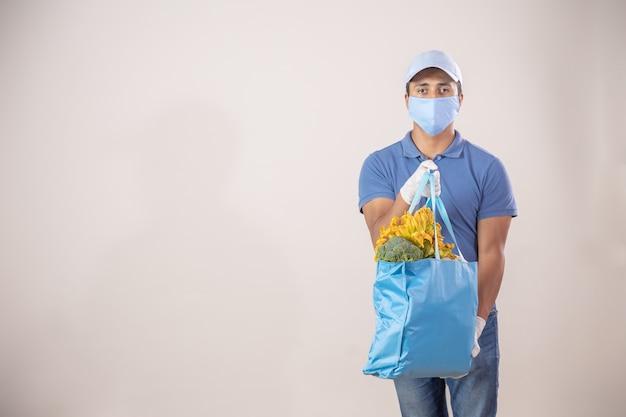 フェイスマスクと手袋を身に着けている果物と野菜の生態学的なバッグを持つメキシコの配達人 Premium写真