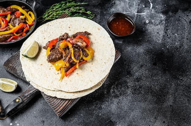 Мексиканские фахитас с цветным перцем и луком, подается с лепешками и сальсой Premium Фотографии