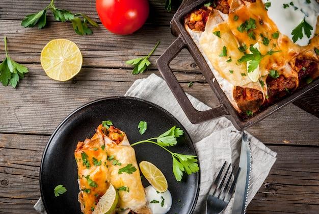 Мексиканская еда. кухня южной америки. традиционное блюдо из острой говяжьей энчиладас с кукурузой, фасолью, помидорами. на противень, на старый деревенский деревянный фон. скопировать вид сверху Premium Фотографии