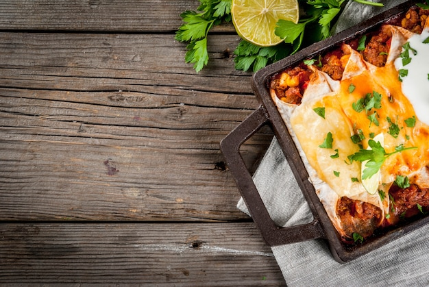 Мексиканская еда. кухня южной америки. традиционное блюдо из острой говяжьей энчиладас с кукурузой, фасолью, помидорами. на противень, на старый деревенский деревянный фон. вид сверху копией пространства Premium Фотографии