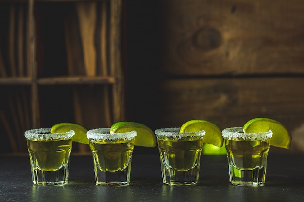 Mexican gold tequila shot with lime and salt on black stone table surface Premium Photo