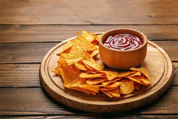 Mexican nachos chips with barbecue sauce. Premium Photo