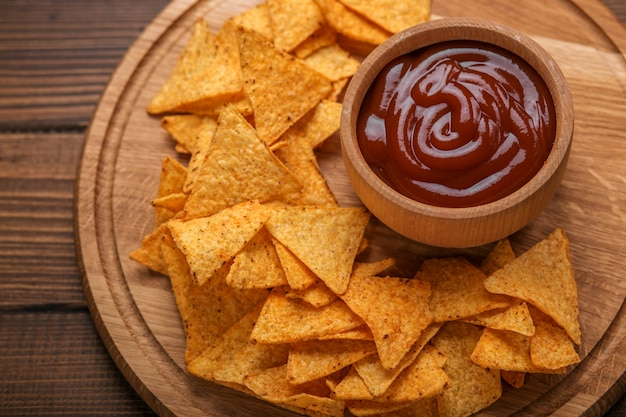 Mexican nachos chips with spicy tomato sauce on wooden background Premium Photo