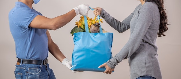 メキシコの保護された配達人が果物と野菜のエコバッグを女性に配達 Premium写真