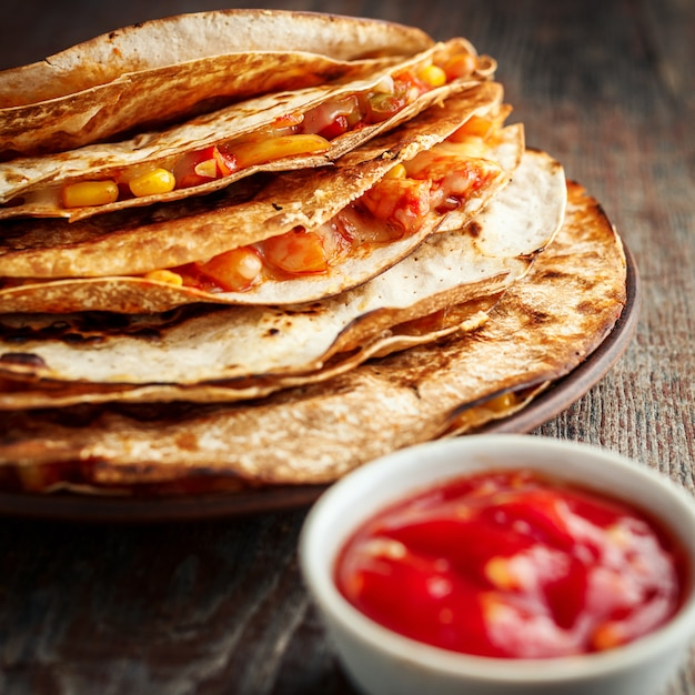 Mexican quesadilla and salsa on a wooden table Premium Photo