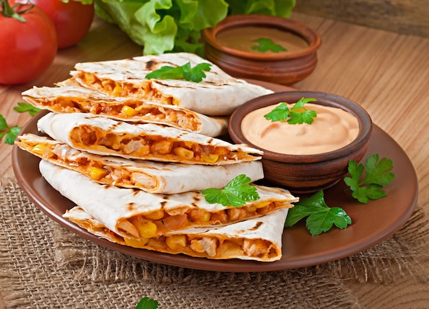 Mexican quesadilla sliced with vegetables and sauces on the table Free Photo