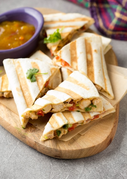 Mexican quesadilla with chicken, tomatoes, cheese and grilled sauce. Premium Photo