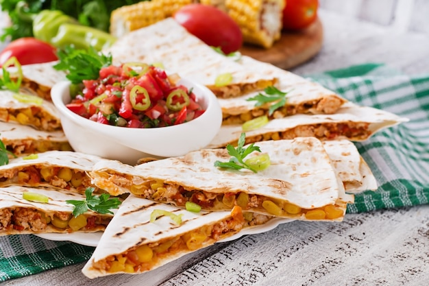 Mexican quesadilla wrap with chicken, corn and sweet pepper and salsa Free Photo