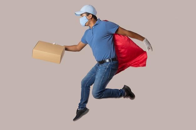 コロナウイルスのパンデミックと手袋をはめて飛んでいるグローブのためにフェイスマスクを着用しているメキシコの赤い帽子の宅配便 Premium写真