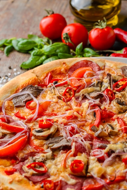 Mexican spicy pizza and ingredients on a wooden table. traditional italian cuisine. party food Premium Photo