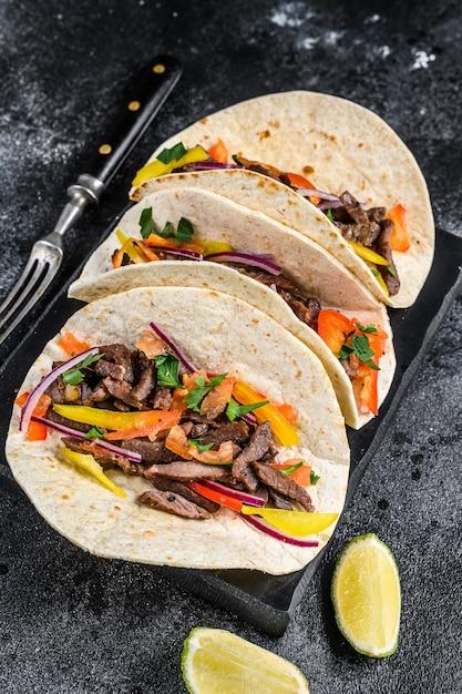 Ракушки тако по-мексикански с говядиной, луком, помидорами и сладким перцем Premium Фотографии