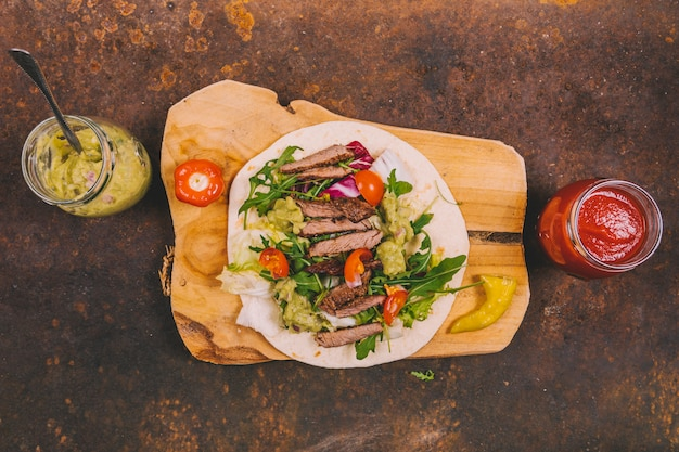 Mexican tacos with beef; fresh vegetables and guacamole with salsa sauce on rusty background Free Photo