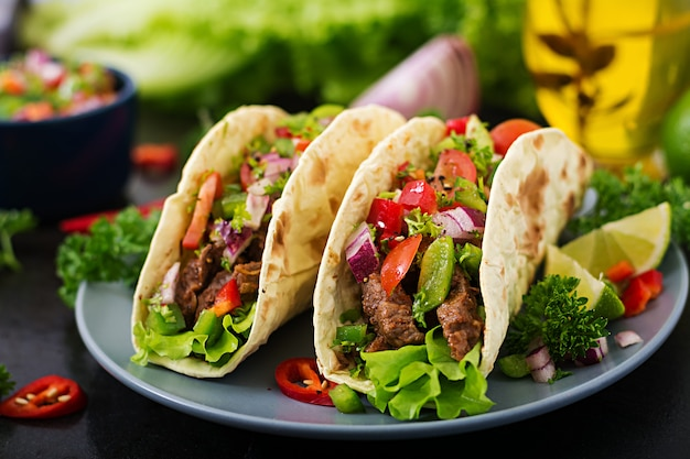 Mexican tacos with beef in tomato sauce and salsa Free Photo