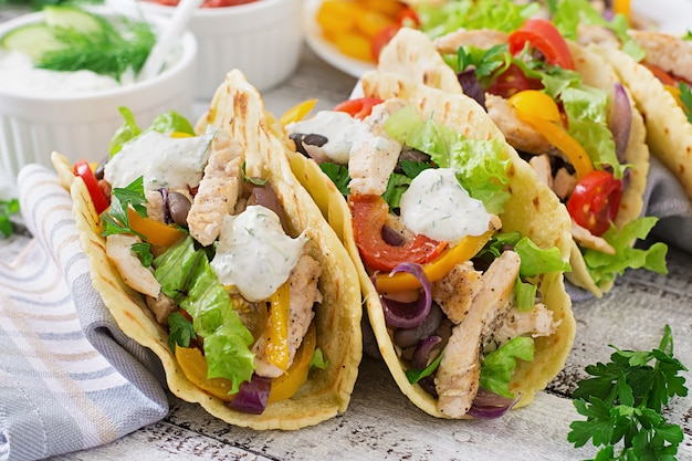 Mexican tacos with chicken, bell peppers, black beans and fresh vegetables Free Photo