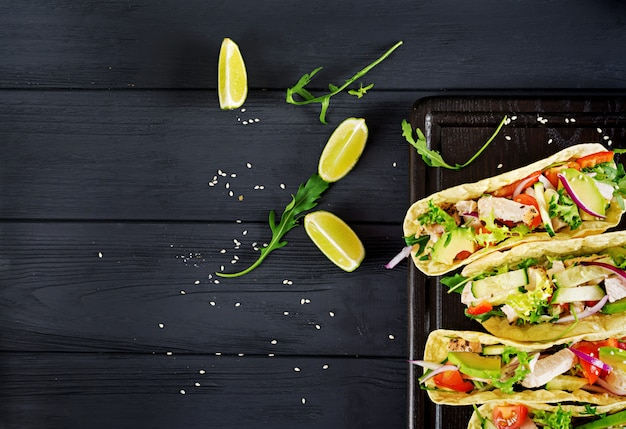 Mexican tacos with chicken meat, avocado, tomato, cucumber and red onion. healthy tortilla. wrap food. taco. top view Premium Photo