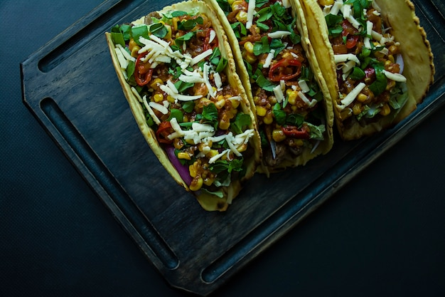 Mexican tacos with meat, cheese, corn, onions and pork herbs on a wooden board Premium Photo
